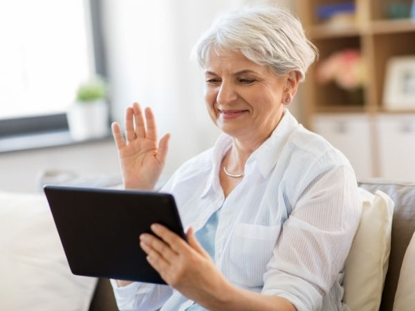 A mature lady sits in her living room chatting on video call communications