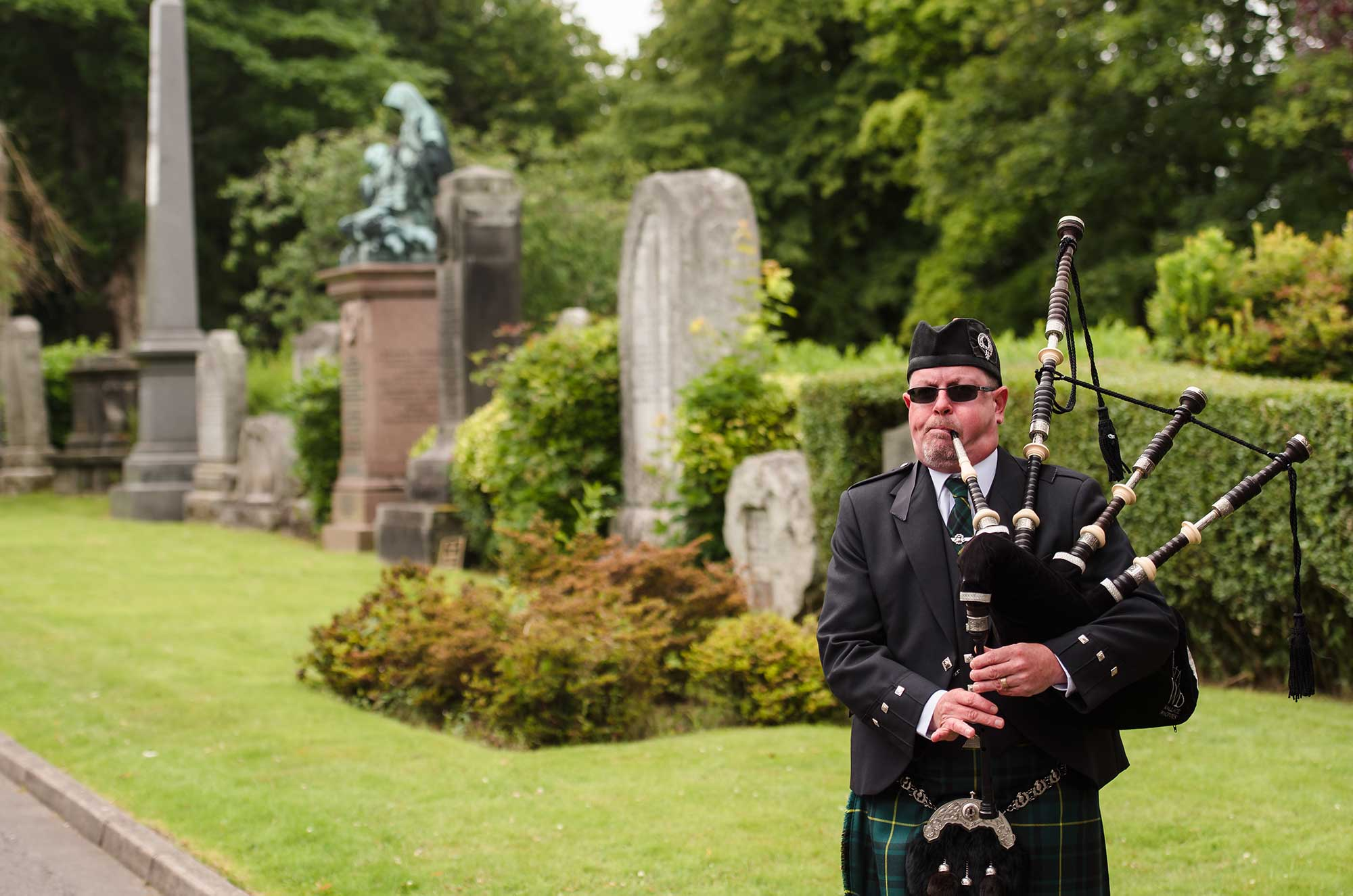 A piper plays the bagpipes at Woodside Cemetery