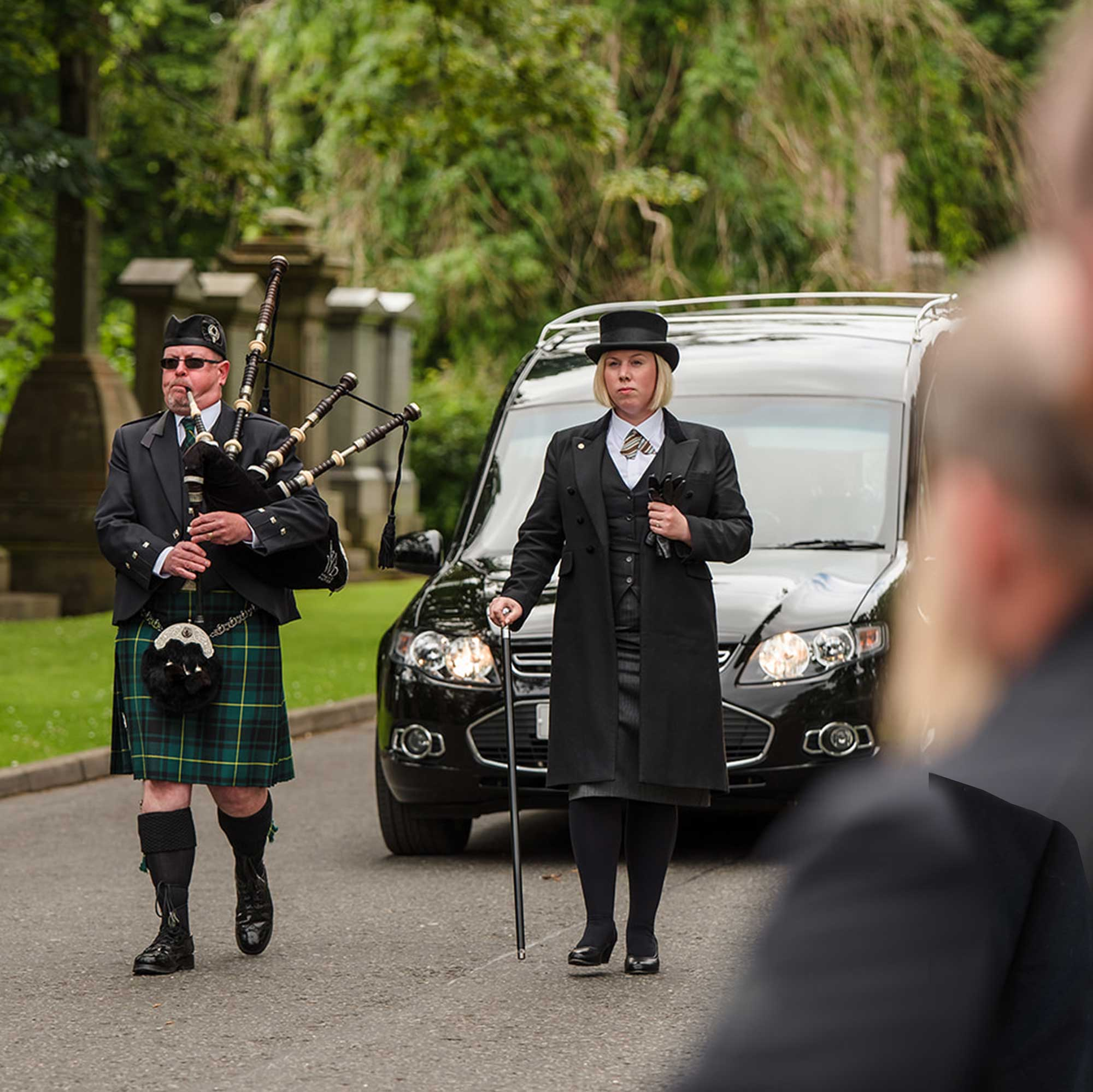 A piper and a funeral director walk in front of the hearse in the grounds of Woodside