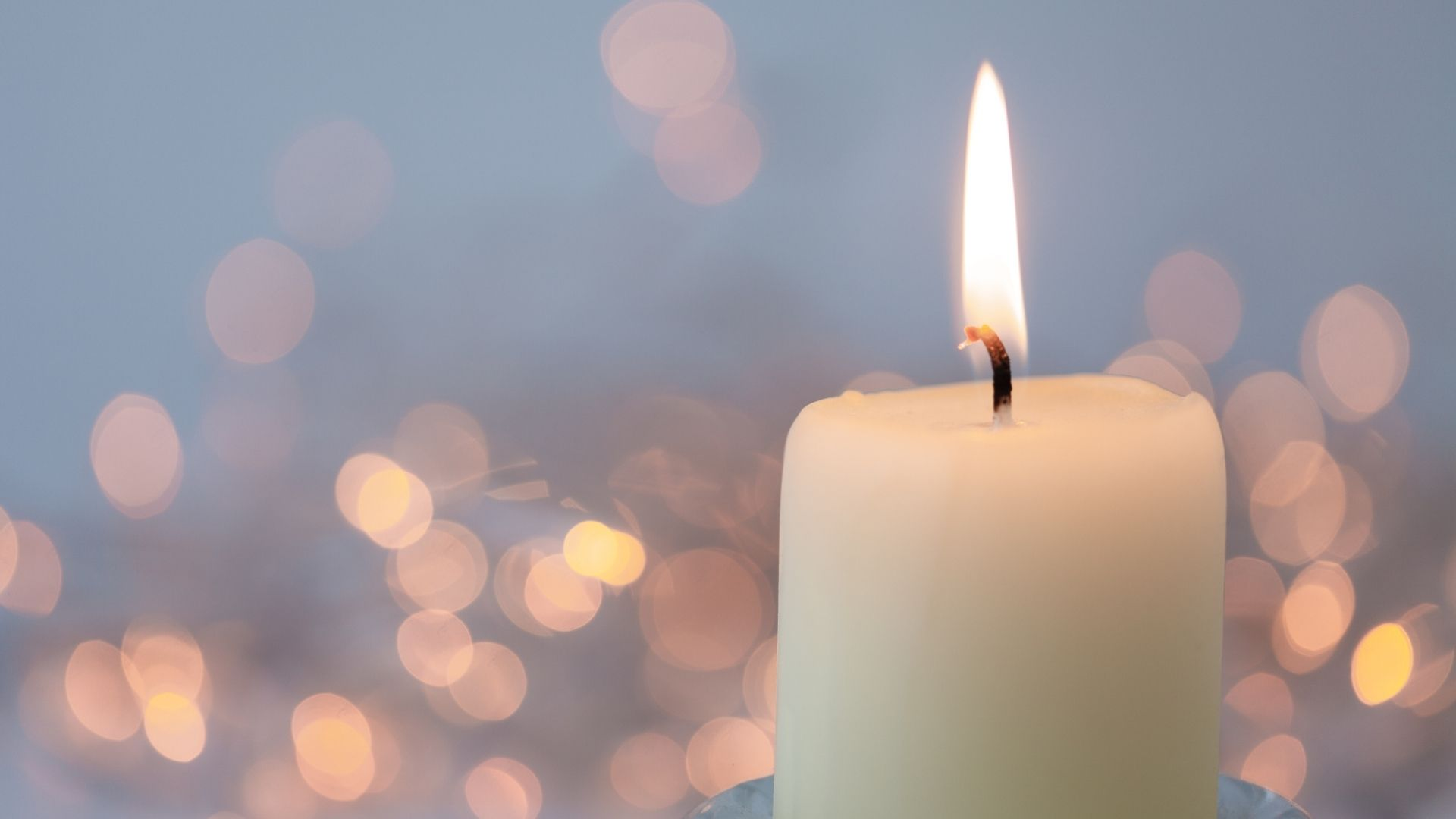 A white lit candle with blurred sparkling candles in the background