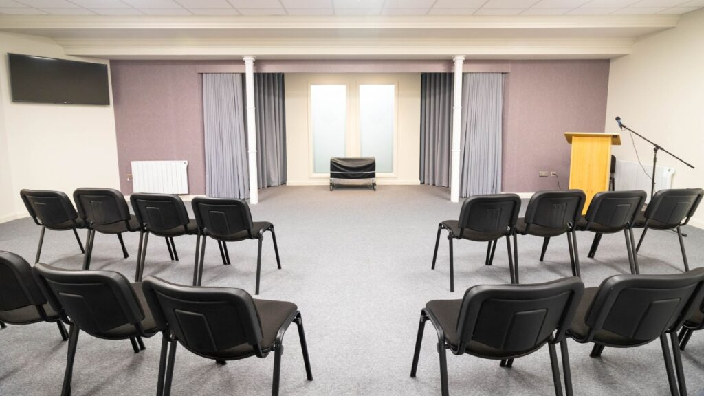 The service room with curtains, rows of chairs and neutral decor
