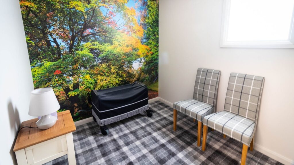 A viewing room with two chairs, a lamp and a grey tartan carpet, the feature wall is of a woodland