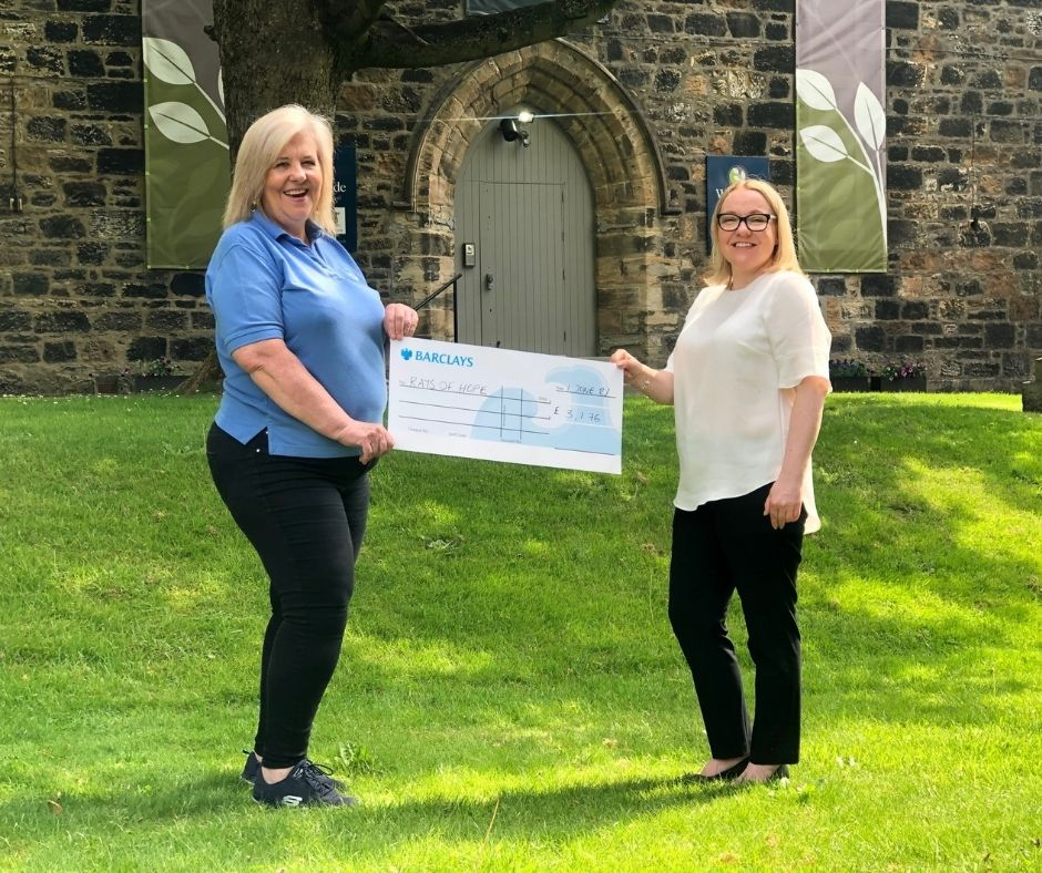 A volunteer from Ray of Hope receives a cheque from Woodside Crematorium manager Katrina