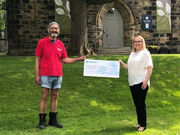 A volunteer from Renfrewshire Foodbank receives a charity cheque outside Martyrs Chapel from Woodside Crematorium manager Katrina