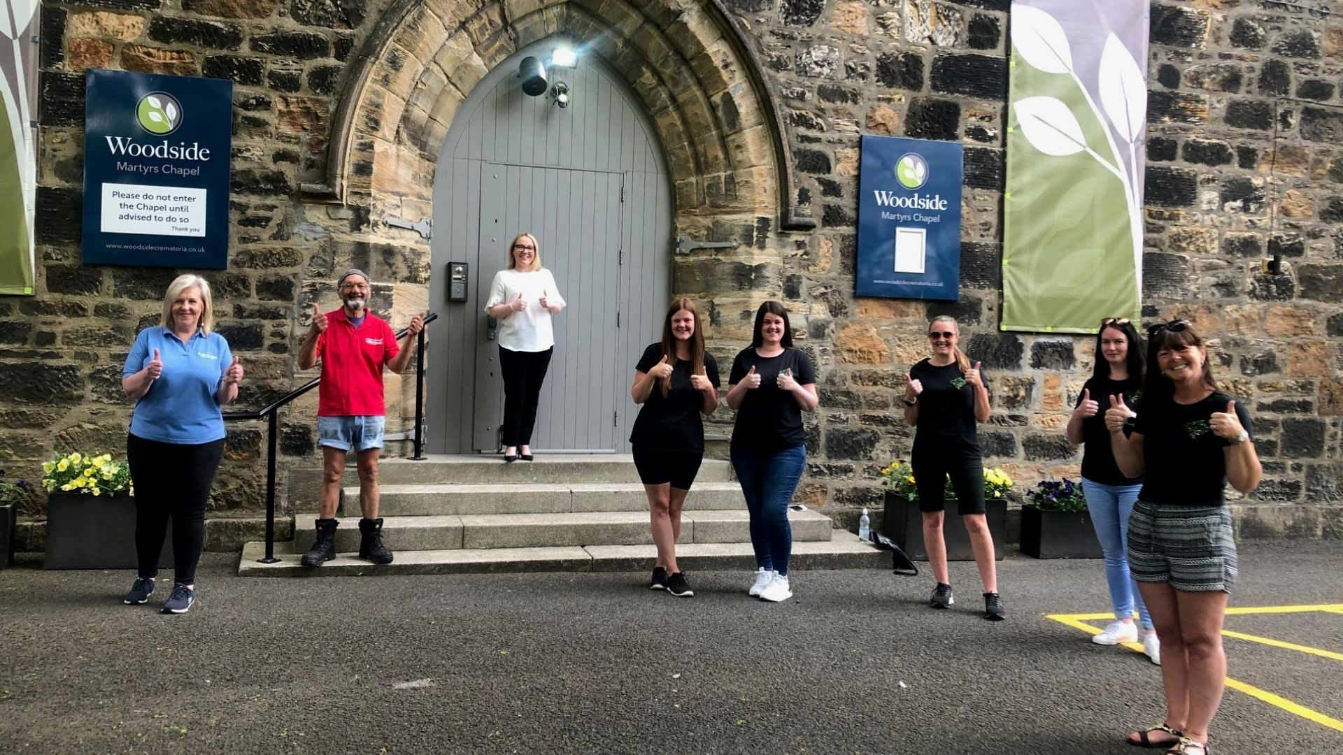 Charity representatives stand outside Martyr's Chapel giving a thumbs up before receiving funds