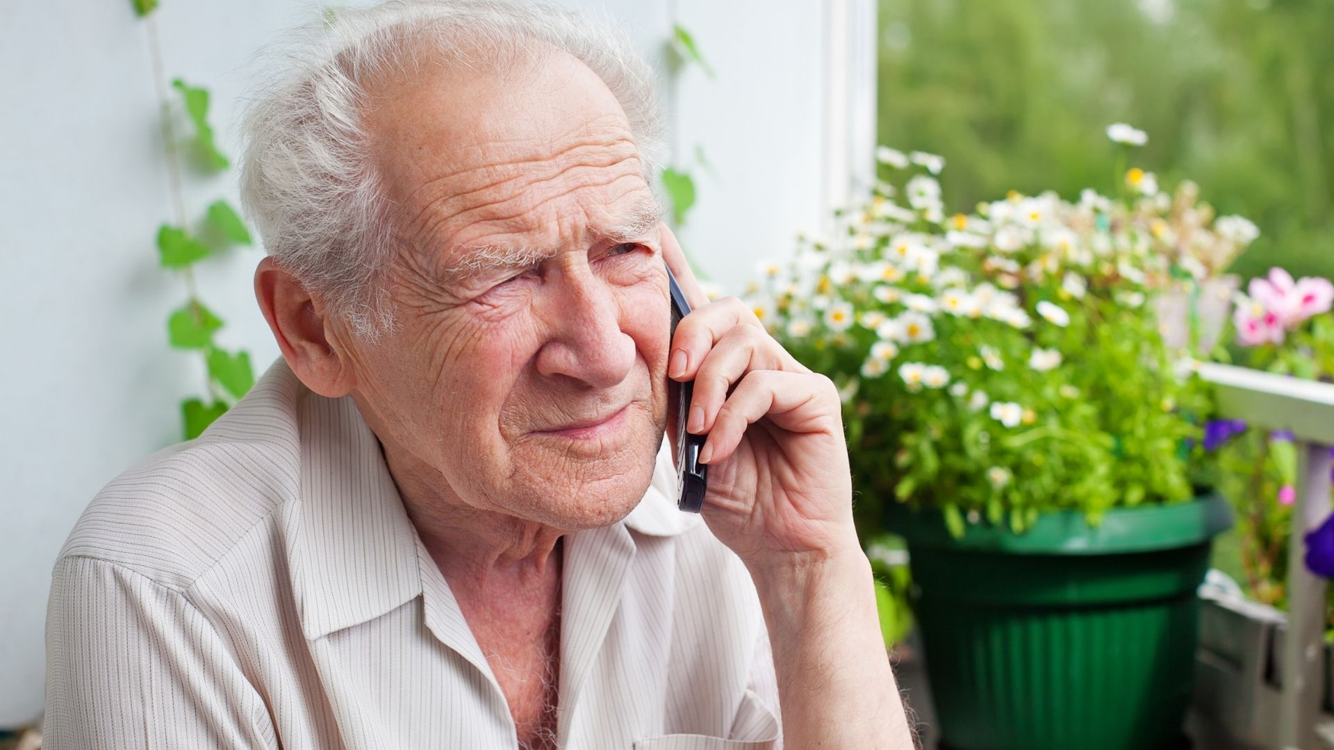 an older man sits with a phone pressed to his ear